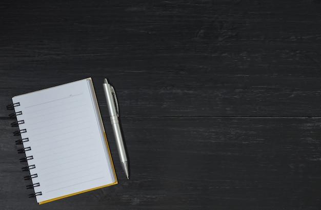 Vue de dessus du livre ouvert. livre ouvert avec un stylo sur fond en bois et espace de la copie pour insérer du texte.
