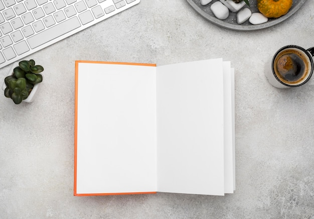 Vue de dessus du livre relié ouvert sur le bureau avec du café