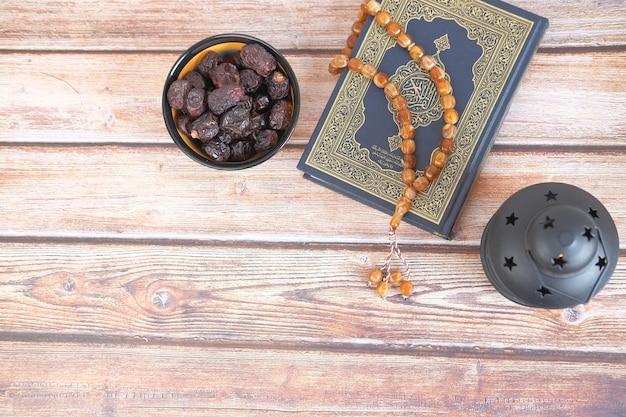 Vue de dessus du livre saint de fruits date coran et chapelet sur table
