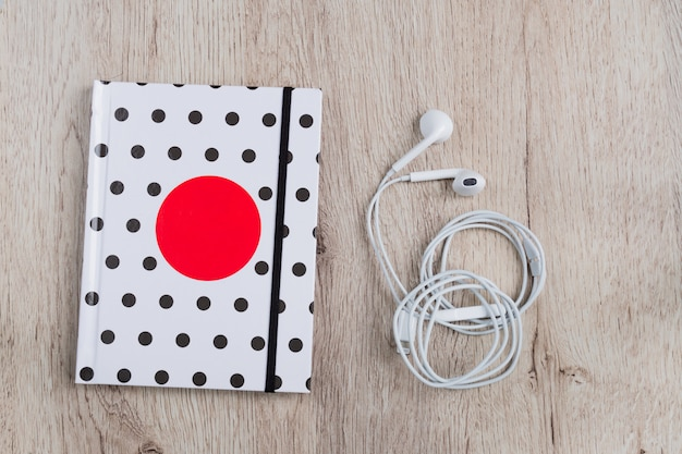 Vue de dessus du livre de voyage avec couverture à pois et un casque blanc sur une table en bois. lay plat minimal.