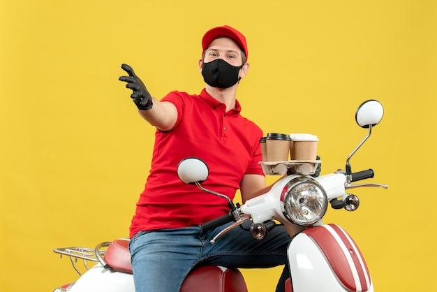 Vue de dessus du livreur ambitieux portant des gants uniformes et chapeau en masque médical assis sur un scooter montrant des commandes parlant de quelque chose