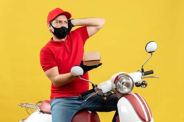 Vue de dessus du livreur choqué portant un chemisier rouge et des gants de chapeau dans un masque médical assis sur un scooter montrant l'ordre
