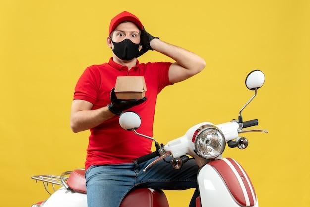 Vue de dessus du livreur émotionnel choqué portant un chemisier rouge et des gants de chapeau en masque médical assis sur un scooter montrant l'ordre
