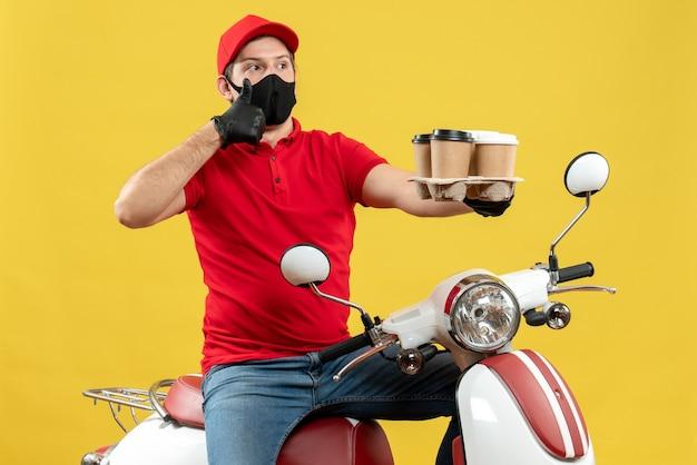 Vue de dessus du livreur émotionnel fier confiant portant des gants uniformes et chapeau en masque médical assis sur un scooter montrant les commandes faisant le geste ok