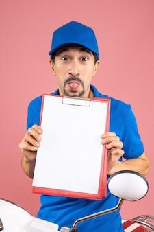 Vue de dessus du livreur masculin émotionnel fou portant un chapeau assis sur un scooter montrant le document