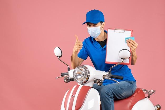 Vue de dessus du livreur masculin en masque portant un chapeau assis sur un scooter montrant un document et une carte bancaire faisant un geste correct sur fond de pêche pastel