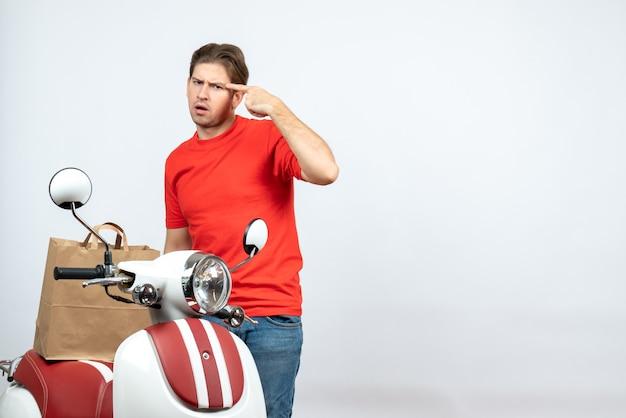 Vue de dessus du livreur de pensée en uniforme rouge debout près de l'ordre de maintien du scooter sur le mur blanc
