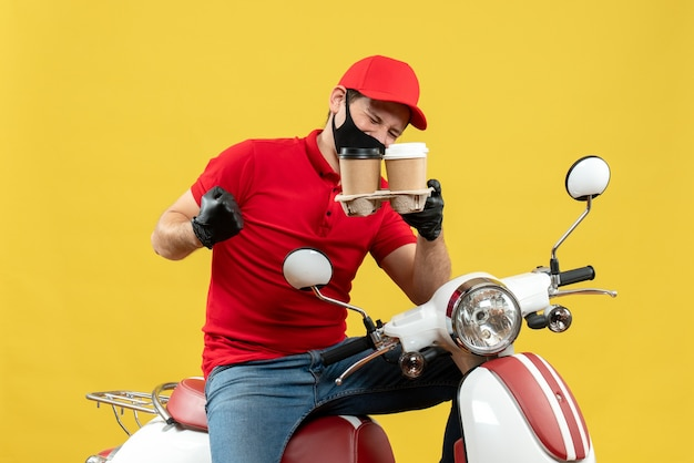 Vue de dessus du livreur portant des gants uniformes et chapeau en masque médical assis sur un scooter montrant les commandes se sentir fier