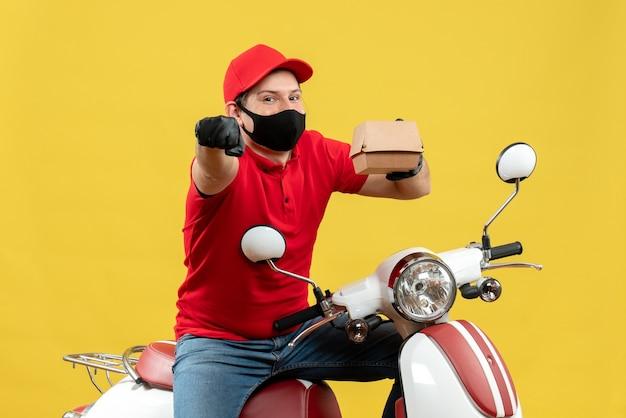 Vue de dessus du livreur de sumiling portant un chemisier rouge et des gants de chapeau en masque médical assis sur un scooter montrant l'ordre pointant vers l'avant