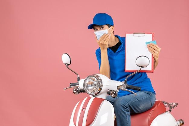 Vue de dessus du livreur surpris en masque portant un chapeau assis sur un scooter montrant un document et une carte bancaire sur une pêche pastel
