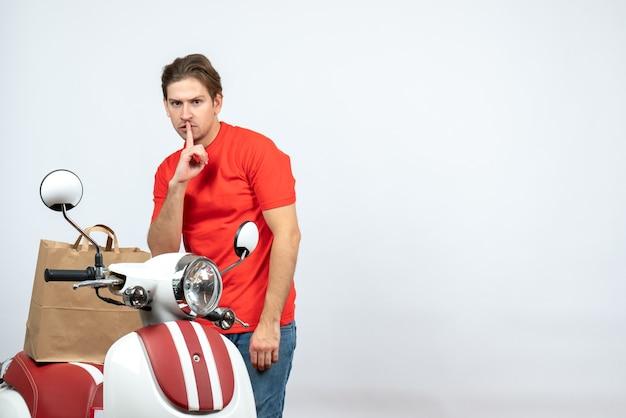 Vue de dessus du livreur en uniforme rouge debout près de scooter faisant un geste de silence sur fond blanc