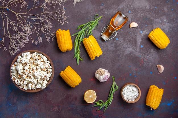Vue de dessus du maïs soufflé frais avec des cors jaunes crus sur la surface sombre de l'usine de film de maïs soufflé