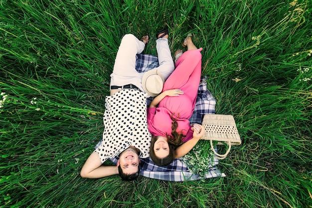 Vue de dessus du mari avec femme enceinte. homme et femme se trouvent sur une couverture parmi les hautes herbes. sac avec un bouquet de fleurs et canotier.