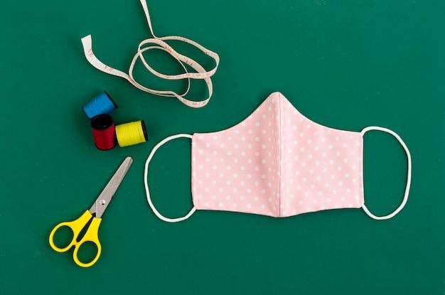 Vue de dessus du masque de coton en tissu bricolage sur tapis de coupe vert