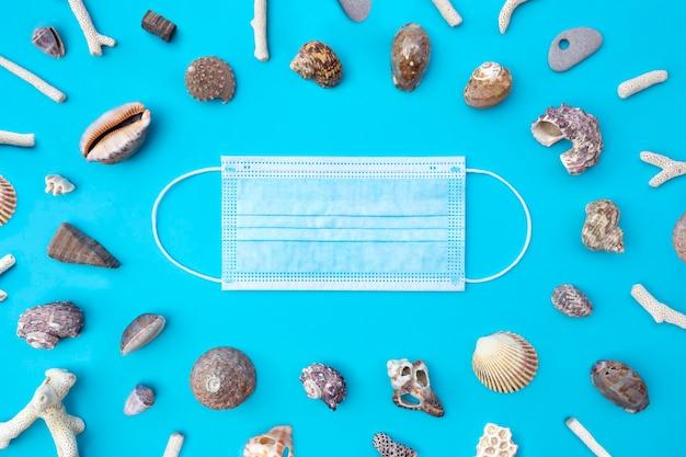 Vue de dessus du masque médical et des coquillages sur bleu. mise à plat