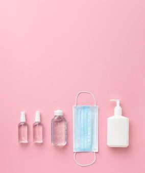 Vue de dessus du masque médical avec désinfectant pour les mains et bouteille de savon liquide