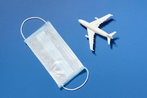 Vue de dessus du masque médical et figurine d'avion
