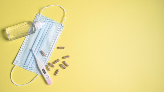 Vue de dessus du masque médical avec thermomètre et pilules