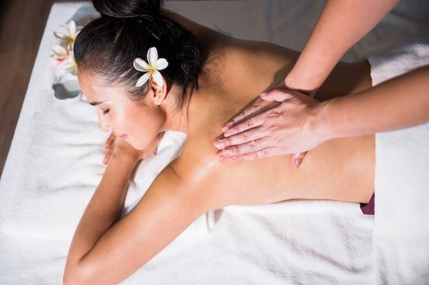Vue de dessus du massage en spirale du dos à l'huile thaïlandaise pour une jeune belle femme asiatique