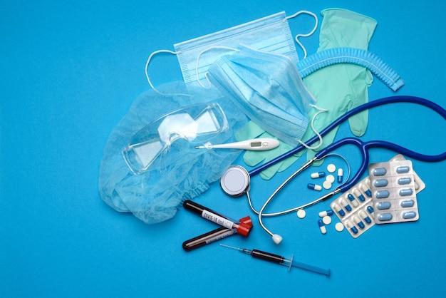 Vue de dessus du matériel médical et des outils sur fond bleu - stéthoscope, masque chirurgical, gants médicaux, seringue et tube à essai sanguin - concept de soins de santé et de médecine.