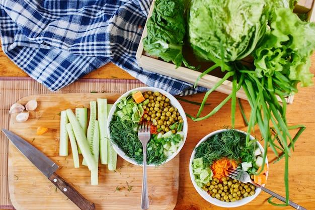 Vue de dessus du mélange de légumes dans des bols avec pois verts, concombres, carottes, laitue et aneth