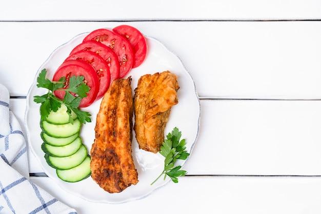 Vue de dessus du merlu frit avec des légumes servis sur une assiette sur fond de bois blanc copie s...
