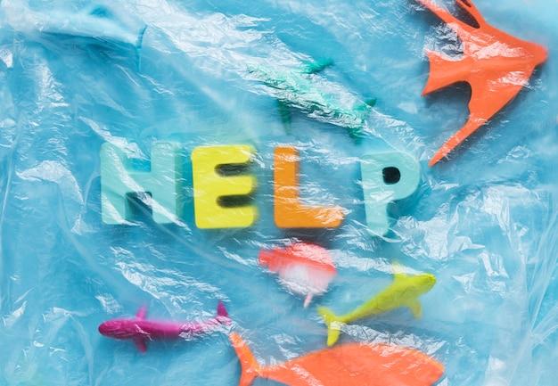 Vue de dessus du message avec des figurines de poissons sous pellicule plastique