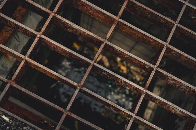 Vue de dessus du métal vieux et rouillé couvert sur le tuyau de vidange de la rue
