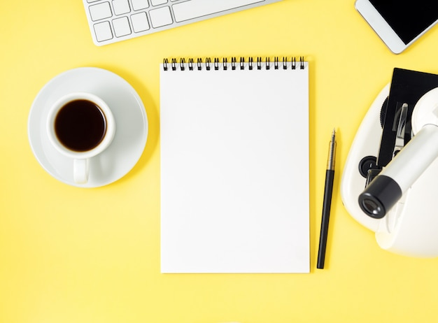 Vue de dessus du microscope de bureau jaune, bloc-notes, ordinateur, smartphone.