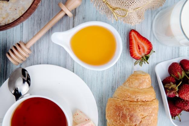 Vue de dessus du miel dans une soucoupe avec croissant fraises mûres fraîches servi avec une tasse de thé sur rustique