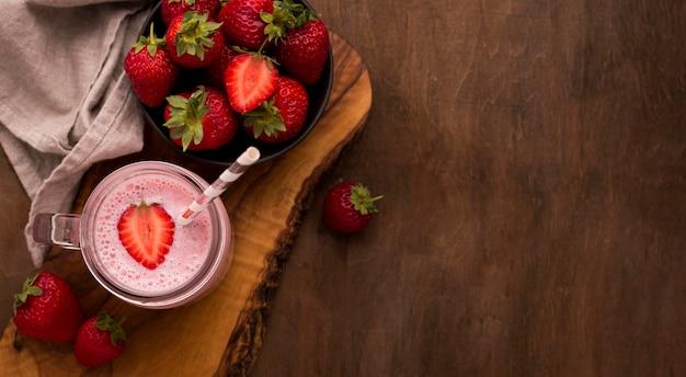 Vue de dessus du milkshake aux fraises avec paille et espace copie