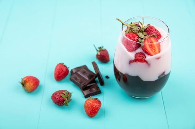 Vue de dessus du milkshake sur un verre avec du chocolat et des fraises avec barre de chocolat sur une surface bleue
