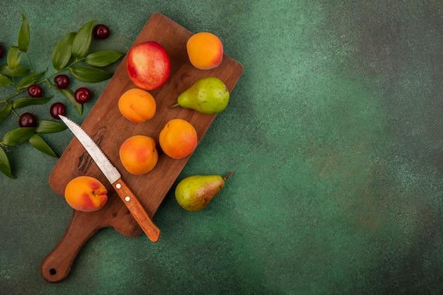 Vue de dessus du modèle de fruits comme les abricots pêche et poire avec couteau sur planche à découper et cerises avec des feuilles sur fond vert avec espace copie