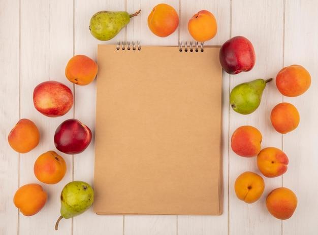 Vue de dessus du modèle de fruits comme pêche abricot et poire autour du bloc-notes sur fond de bois avec espace copie