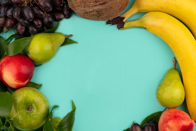 Vue de dessus du modèle de fruits comme pomme de banane raisin pêche poire de noix de coco avec des feuilles sur fond bleu avec espace de copie