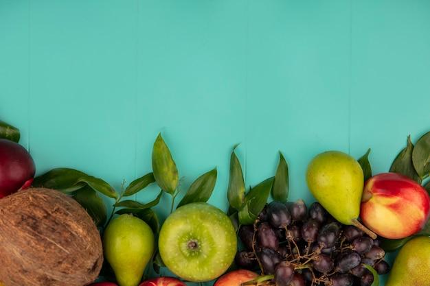 Vue de dessus du modèle de fruits comme pomme de raisin pêche poire de noix de coco avec des feuilles sur fond bleu avec espace de copie