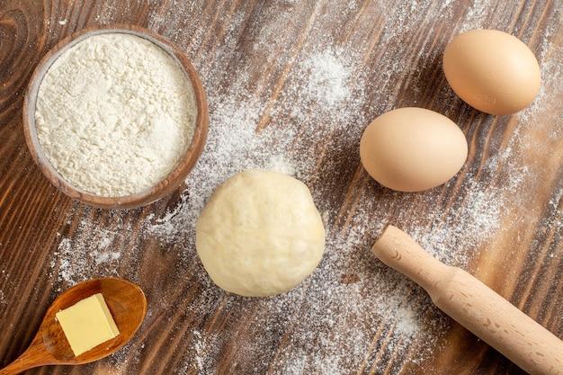 Vue de dessus du morceau de pâte crue avec de la farine et des œufs sur une pâte de bureau en bois cuire des œufs crus