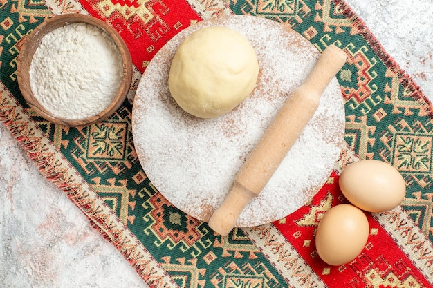 Vue de dessus du morceau de pâte crue avec de la farine sur le tapis coloré et la farine de farine de fond blanc cuire la pâte