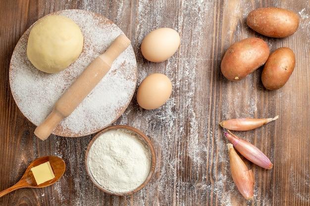 Vue de dessus du morceau de pâte crue avec des pommes de terre à la farine et des œufs sur un bureau en bois