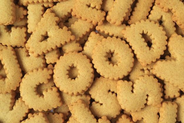 Vue de dessus du mot good orthographié avec des biscuits en forme d'alphabet sur le tas des mêmes biscuits