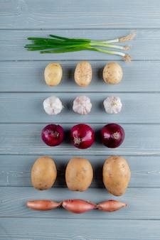 Vue de dessus du motif de légumes comme oignon ail ailé pomme de terre sur fond de bois