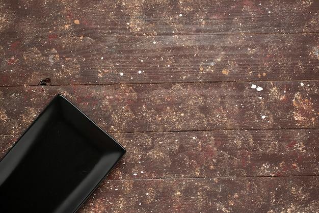 Vue de dessus du moule vide noir isolé sur brun rustique, four à gâteaux en bois en bois
