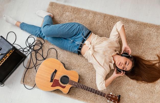 Vue de dessus du musicien féminin sur le sol à la maison avec un casque et une guitare acoustique