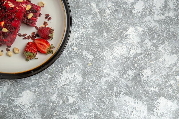Vue de dessus du nougat rouge tranché avec des noix et des fraises rouges fraîches sur une surface blanche
