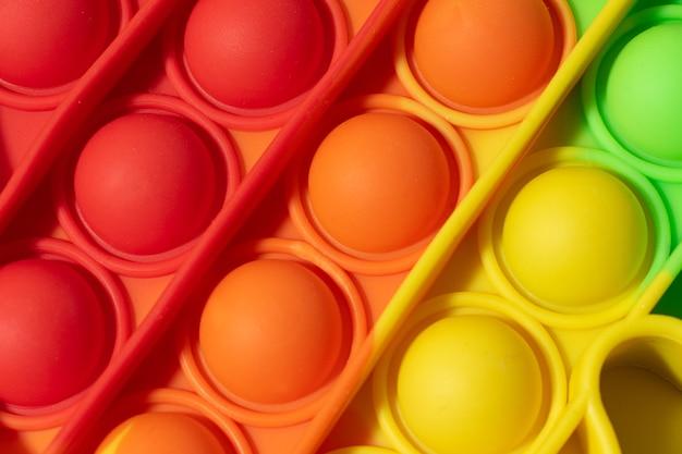 Vue de dessus du nouveau jouet sensoriel - pop it.couleur arc-en-ciel, macro photohraphie de bulles.forme silicone
