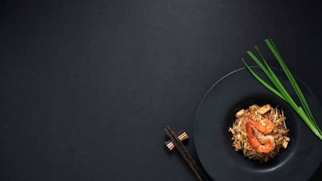 Vue de dessus du pad thai, remuer la mouche de nouilles thaï aux crevettes et oeuf dans une assiette en céramique noire sur tableau noir