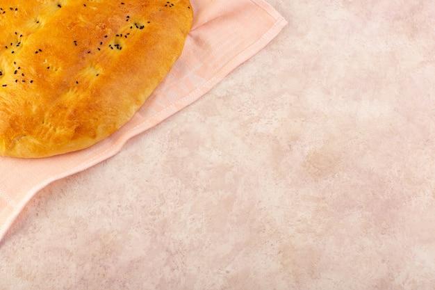 Une vue de dessus du pain cuit chaud savoureux enveloppé dans une serviette rose sur rose