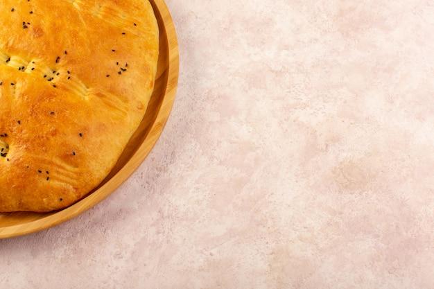 Une vue de dessus du pain cuit chaud savoureux frais à l'intérieur du bureau rond sur rose