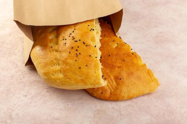 Une vue de dessus du pain cuit chaud savoureux frais à moitié tranché à l'intérieur et à l'extérieur des paquets de papier sur rose