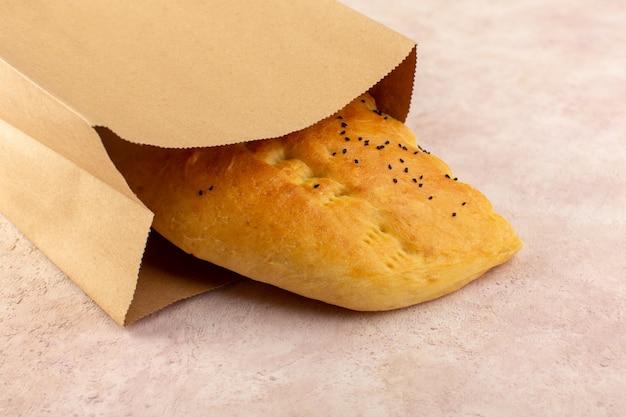 Une vue de dessus du pain cuit chaud savoureux frais à moitié tranché à l'intérieur des paquets de papier sur rose